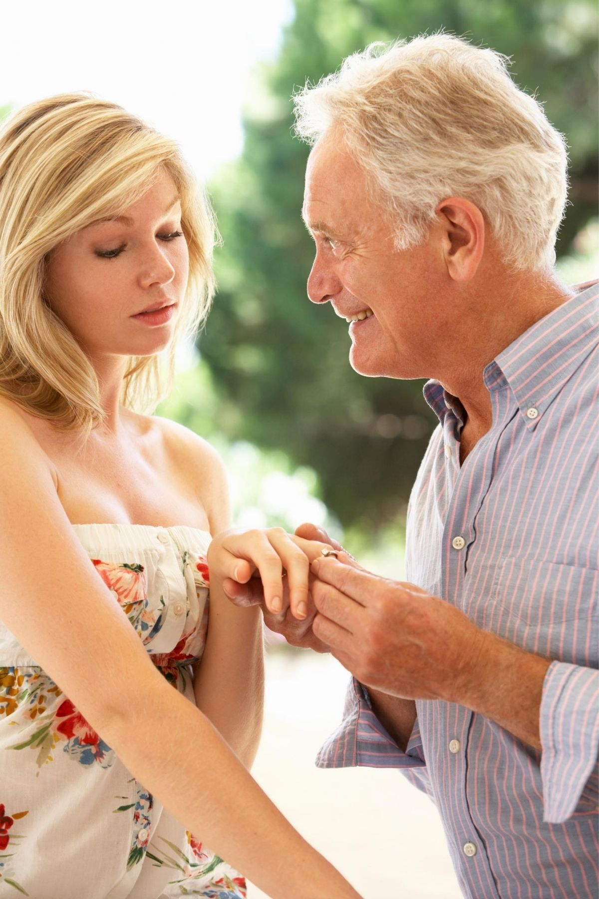 older man putting an engagement ring on a younger woman